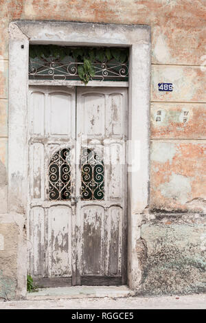 Abandoned Doorway in Merida: A once white door seems abandones with plants breaking through the skylight window, rust on the decorative lattice and a large padlock and chain. - Stock Image