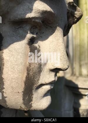 Tombstone sculpture with acid rain tears. Brompton cemetery, Kensington, London, England - Stock Image