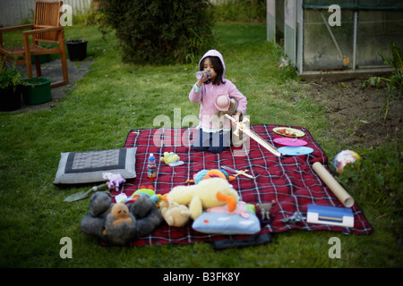 Picnic in the garden Five year old girl drinks juice from a bottle amongst soft toys laid out on picnic blanket - Stock Image