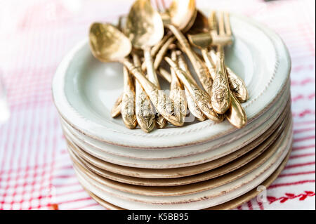 small plates with golden silverware - Stock Image