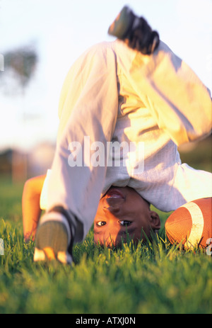 6 year old African American boy attempting headstand in grass park - Stock Image