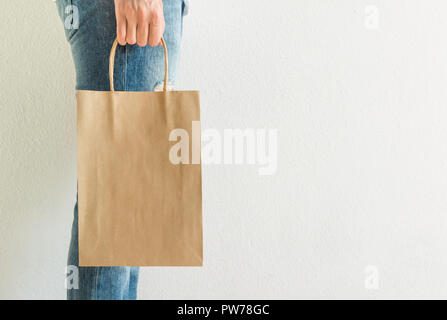 Young caucasian woman girl in jeans holds in hand empty blank mock up brown craft paper bag white wall background. Christmas New Year present shopping - Stock Image