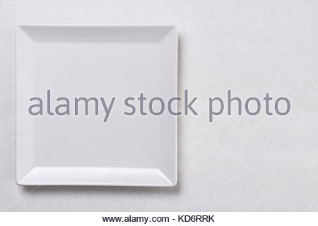 Flat lay above white square plate on the white marble background table. - Stock Image