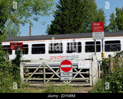 A Greater Anglia Regional Train crossing a Old Level Crossing with Warning Signs to the east of Norwich, Norfolk, - Stock Image