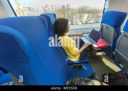 young woman loking in the window with laptop on knees during her traveling in train - Stock Image