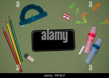 School concept. Smartphone, stationery on green background, blank copy space - Stock Image