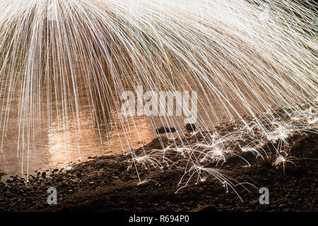 steel wool spinning over water and beach - Stock Image