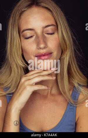 Young woman smiling with eyes closed and hand under chin, portrait - Stock Image
