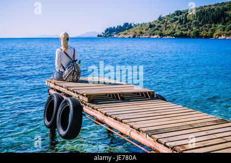 Girl with backpack on pier on the beach near Kalami looking into sea. Corfu Island, Greece - Stock Image