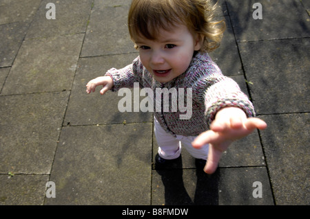 toddler tantrum girl female two years old caucasian pursue chase grab brunette childhood - Stock Image