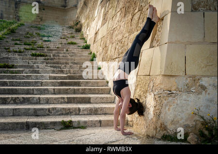 woman doing a handstand against a wall outside - Stock Image