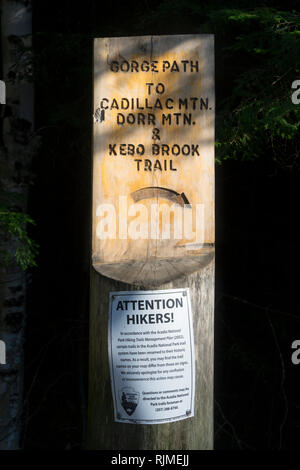 Carved wooden sign for hiking trails in Acadia National Park, Maine, USA. A notice to hikers from National Park Service is screwed to the wooden post. - Stock Image