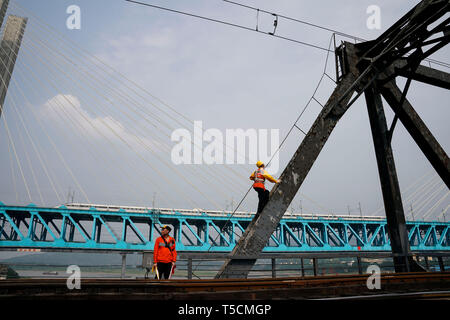 (190423) -- CHONGQING, April 23, 2019 (Xinhua) -- Workers of China Railway Chengdu Group Co., Ltd. conduct final check on the previous Baishatuo Yangtze River railway bridge in Jiangjin of southwest China's Chongqing Municipality, April 23, 2019. The previous Baishatuo Yangtze River railway bridge, completed in 1959, will stop service after April 24. All trains will run on the new double decker steel truss cable stay railway bridge after that day. The new bridge has 4 tracks on the upper deck for passenger trains with a designed speed of 200 kilometers per hour and 2 tracks on the lower deck f - Stock Image