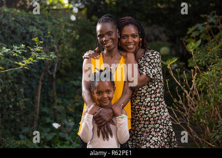 A grandmother, mother, and daughter standing together in a garden - Stock Image