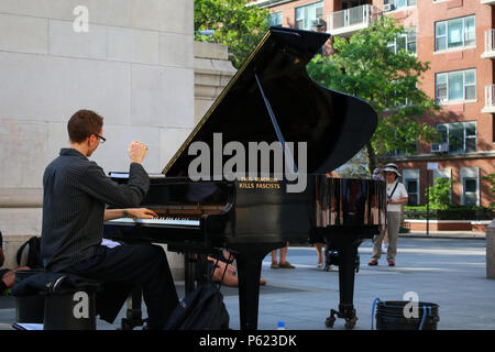 NEW YORK, NY - JULY 2: This Machine Kills Fascists - Col busking by playing grand piano under Washington Square Park arch in West Village, Manhattan o - Stock Image