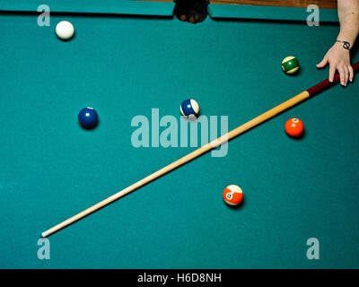 overhead view of womans hand reaching for pool cue on pool table - Stock Image