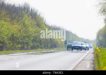 Ashford, Kent, UK. 15th Apr, 2019. UK Weather: Hot and sunny weather on the A259 heading towards Hastings as the hazy hot weather forms a mirage on the asphalt. © Paul Lawrenson 2019, Photo Credit: Paul Lawrenson/ Alamy Live News - Stock Image