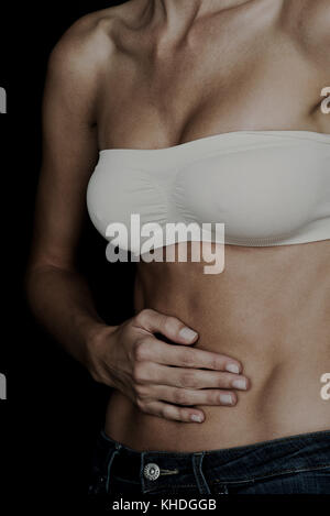 Woman holding hand on bare stomach - Stock Image