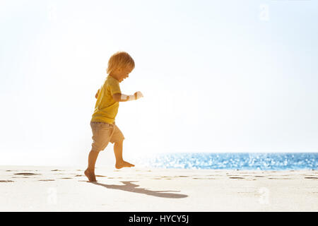 Happy baby walking at lonely beach - Stock Image
