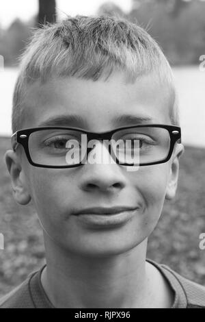 Black and white portrait of a caucasian preteen boy with glasses and a little smirk - Stock Image