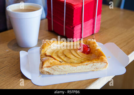 Having apple cake at Coffee Shop. Cake with slice tray, disposable coffee cup and red napkin holder. Selective focus - Stock Image