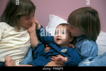 Three siblings, baby, toddler and young girl - Stock Image