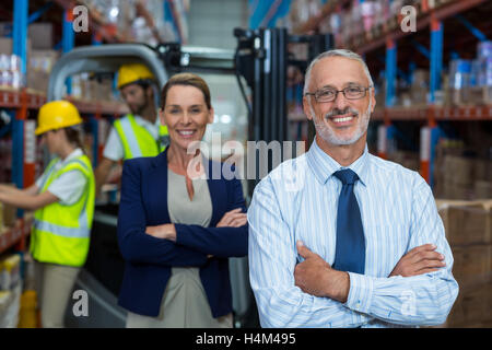 Portrait of warehouse manager and client smiling with arms crossed - Stock Image
