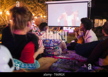 Friends watching movie on projection screen in backyard - Stock Image