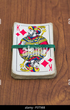 stack of playing cards with king on top and rubber band - Stock Image