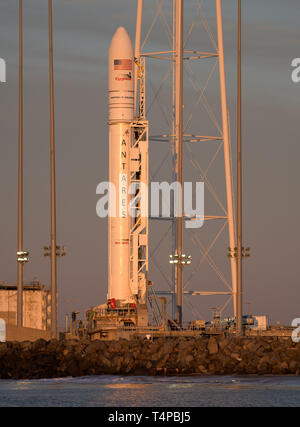 The Northrop Grumman Antares rocket, with Cygnus resupply spacecraft onboard, positioned on lunch Pad-0A at sunrise at the NASA Wallops Flight Facility April 16, 2019  in Wallops, Virginia. The rocket is schedule to deliver 7,600 pounds of science and research, crew supplies and vehicle hardware to the International Space Station on April 17th. - Stock Image