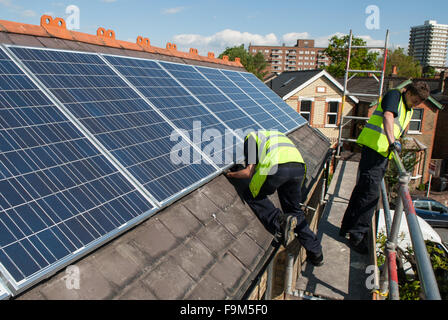 Workers install photovoltaic solar panels on the slate roof of a Victorian house in London, England. - Stock Image
