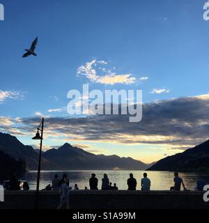 Queenstown in New Zealand at sunset with tourists watching over the waterfront - Stock Image