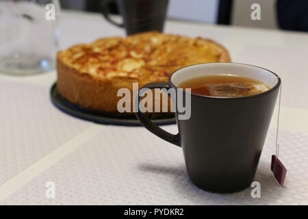 A cup of hot tea with delicious homemade apple pie. Dark grey teacup with a tea bag in and a crunchy apple pie in the background. - Stock Image