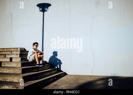 Young male runner resting on sunny urban steps - Stock Image