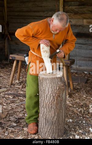 Man cutting woodwork at the openair Viking museum at Trelleborg, Slagelse, Zealand, Denmark - Stock Image