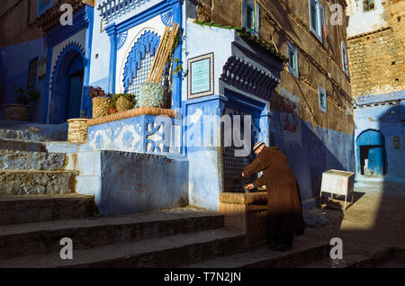 Chefchaouen, Morocco : A man wearing a djellaba fills a bottle of water from a fountain in the blue-washed alleyways of the medina old town. - Stock Image