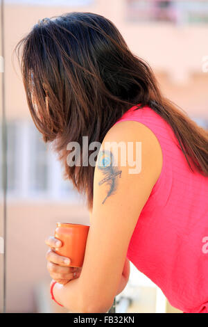 Side profile of a modern Indian woman with tattoo on her arm - Stock Image