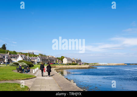 View along waterfront promenade with two women walkin beside Lossie River mouth on Moray Firth coast. Lossiemouth, Moray, Scotland, UK, Britain - Stock Image