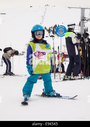 small boy on skis wearing ski clothes and helmet waiting  for a skiing lesson at a ski school collection point - Stock Image