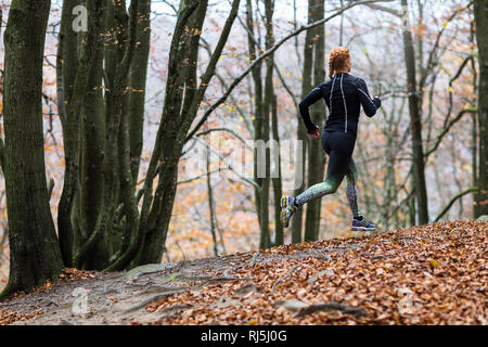 Young woman running in forest - Stock Image