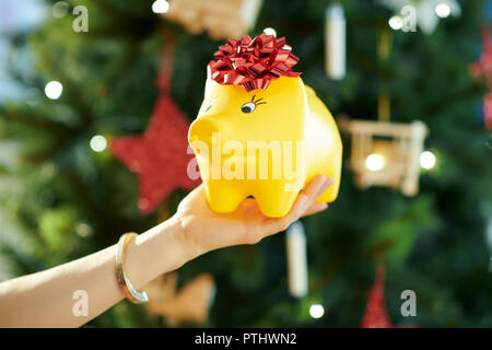 yellow piggy bank with red bow in hand of woman near Christmas tree in a hand of woman - Stock Image