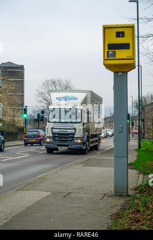 Gatso speed camera and passing lorry and cars on the High Street in Glossop - Stock Image
