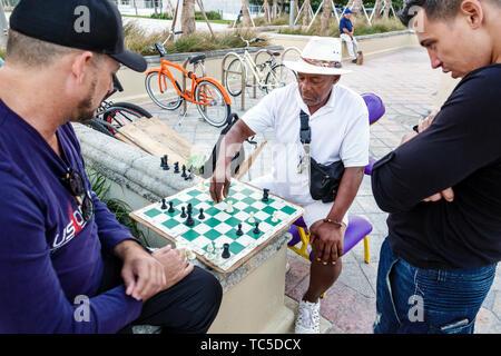 Miami Beach Florida North Beach Atlantic Way chess game Hispanic Black man friends watching strategy playing moving rook making move - Stock Image