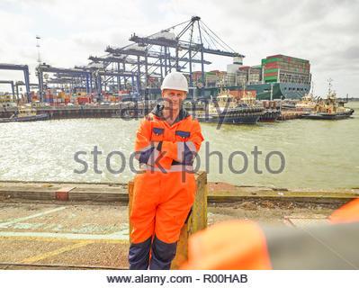 dock worker relaxing infront of cargo ship leaving dockside - Stock Image