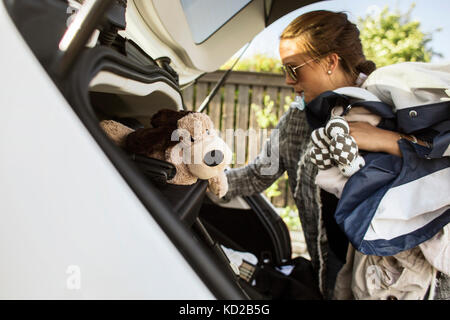 Woman packing clothes into car trunk - Stock Image