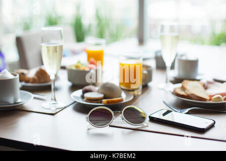 Sunglasses and breakfast on table in cafe - Stock Image