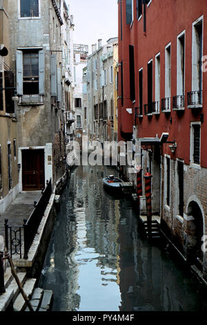Aging palaces line a narrow side canal with boats and a bridge, Venice, Italy - Stock Image