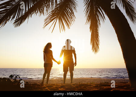 Happy couple sunset beach under palm - Stock Image
