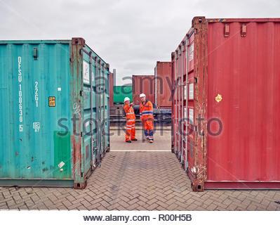 Dock workers between cargo containers at Port of Felixstowe, England - Stock Image