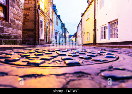 Manhole cover, drain cover, storm drain, metal drain cover, manhole, cover, covers, storm drain cover, drain, Whitby, Yorkshire, UK, England - Stock Image